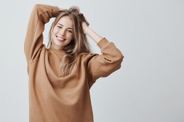 Hermosa mujer encantadora joven rubia encantadora en suéter suelto sonriendo felizmente, divirtiéndose en el interior, jugando con el pelo largo y liso.