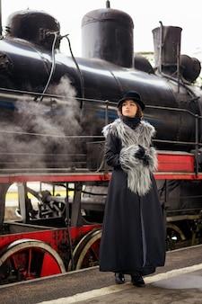 Hermosa mujer se encuentra en la plataforma en el motor con un abrigo vintage
