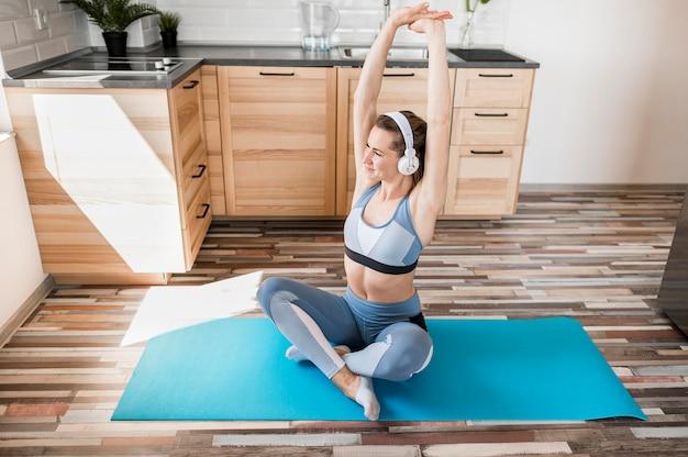 Hermosa mujer entrenando en estera de yoga
