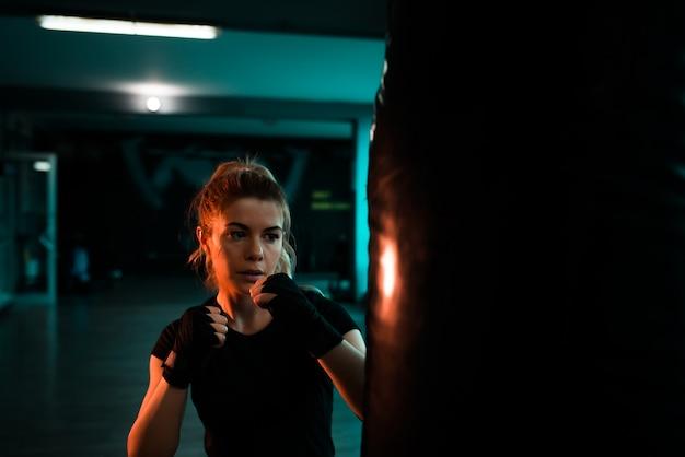 Hermosa mujer entrenando con saco de boxeo. de cerca.
