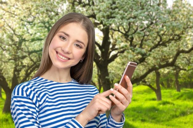 Hermosa mujer enviando mensajes de texto en su teléfono celular