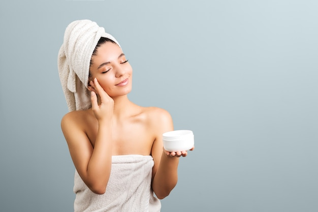 Hermosa mujer envuelta en toallas sosteniendo alegremente un frasco blanco con crema y tocando su rostro