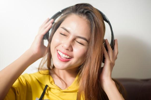 Hermosa mujer es escuchar musica en casa.