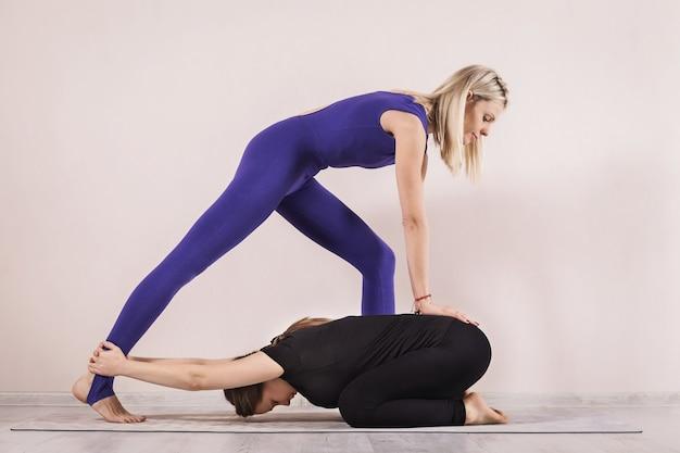 Una hermosa mujer es una rubia, una profesora de terapia de yoga realiza estiramientos de tracción de la columna a un estudiante en la pose de un niño a balasana