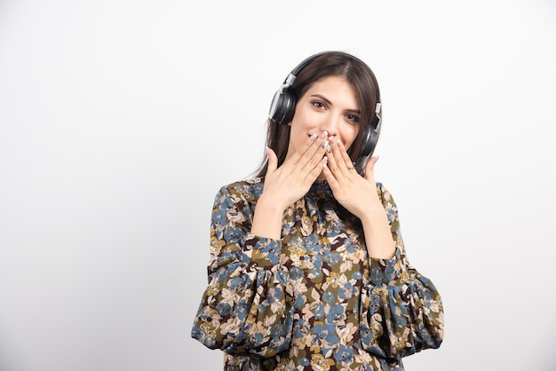 Hermosa mujer escuchando canciones y cerrando la boca sobre fondo blanco.
