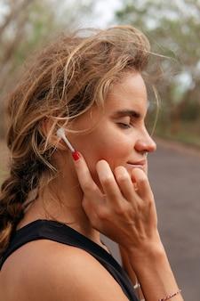 Hermosa mujer escuchando música en el parque