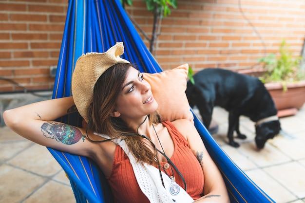 Hermosa mujer española relajante en una hamaca en casa.