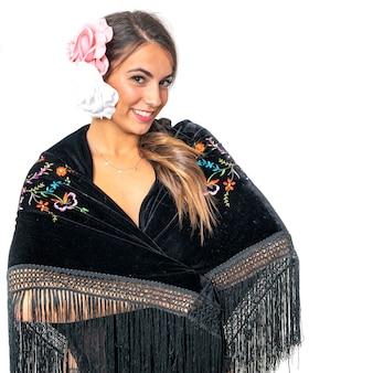 Hermosa mujer española de sevilla y andaluza con cabello castaño vestida con el típico traje de mantón de manila