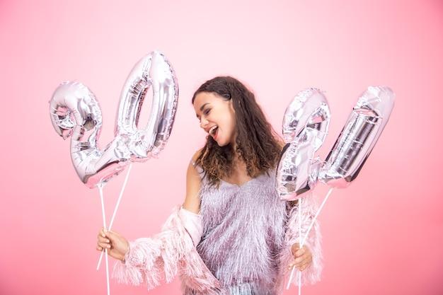 Hermosa mujer en un estado de ánimo festivo sostiene globos plateados para el concepto de año nuevo