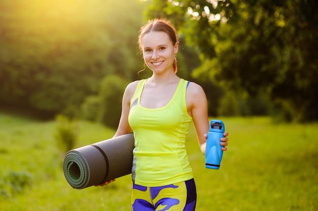 Hermosa mujer con una estera de yoga al aire libre en el parque en la puesta de sol