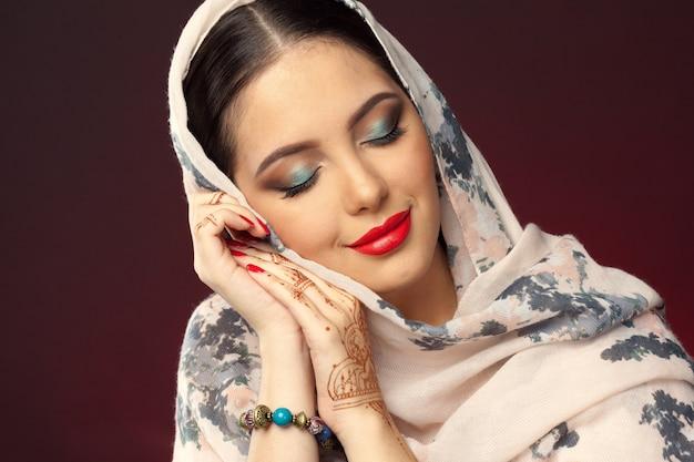 Hermosa mujer en estilo oriental con mehendi sobre fondo oscuro