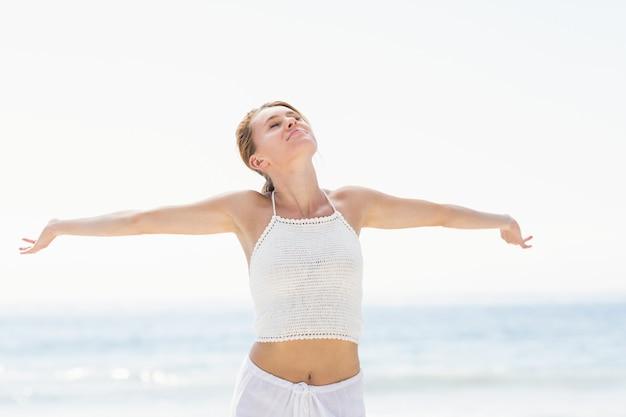 Hermosa mujer estirando los brazos en la playa