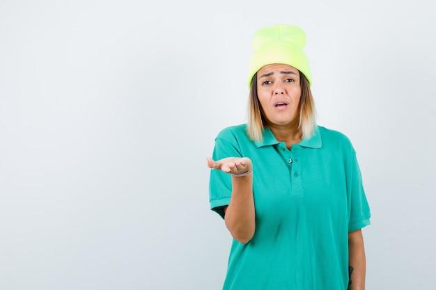 Hermosa mujer estirando la mano a la cámara en camiseta de polo, gorro y mirando desconcertado. vista frontal.