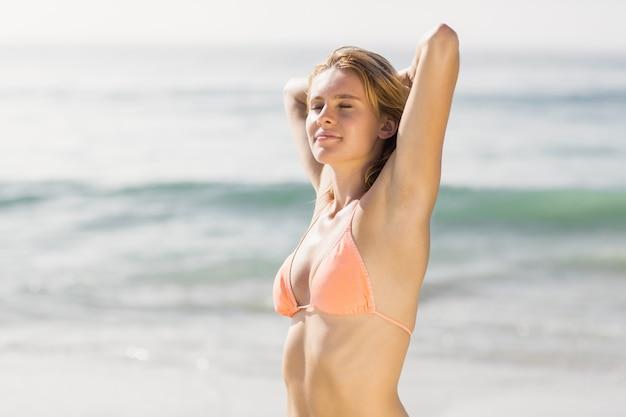 Hermosa mujer estirando en la playa