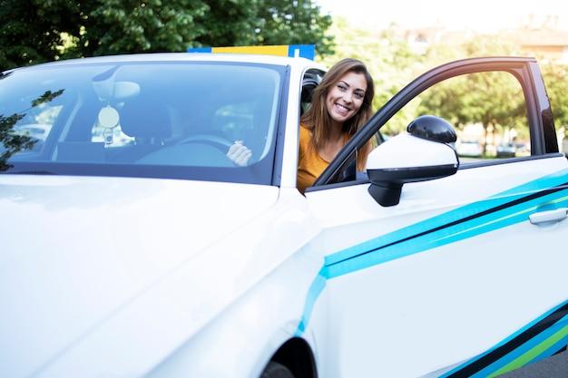Hermosa mujer estudiante de conducción de automóviles entrando en el vehículo en su primera clase