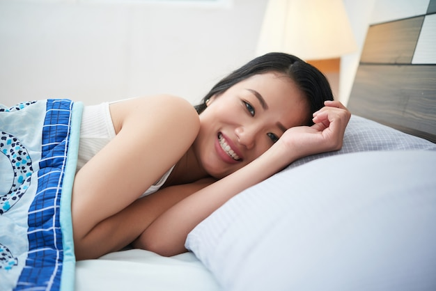 Hermosa mujer étnica abrazados en la cama
