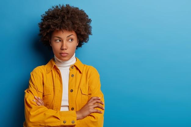 Hermosa mujer étnica mira pensativamente en el lado derecho, mantiene las manos cruzadas sobre el pecho, viste camisa amarilla, posa sobre fondo azul