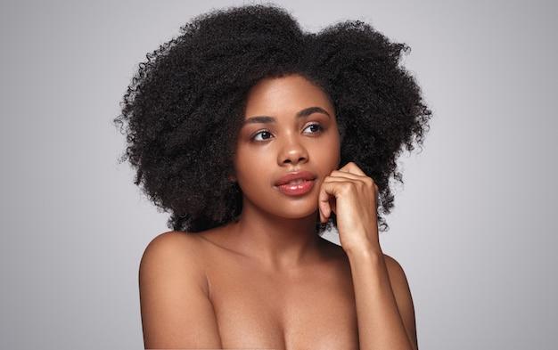 Hermosa mujer étnica con una piel perfecta mirando a otro lado sobre fondo gris