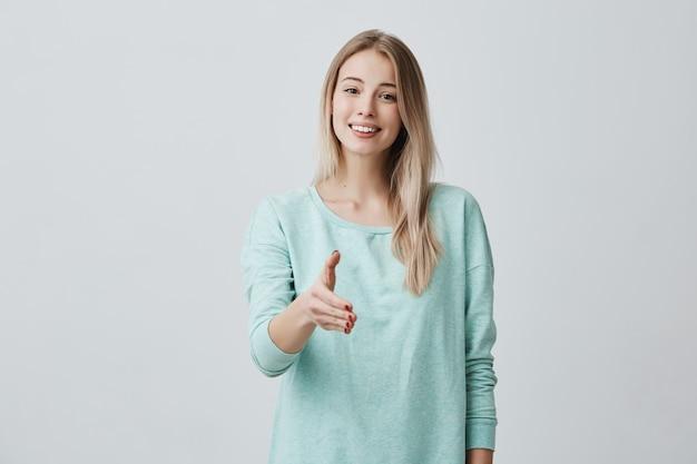 Hermosa mujer europea amigable con cabello largo rubio con suéter informal azul sonriendo ampliamente demostrando sus dientes blancos perfectos y estirando su brazo durante la presentación. lenguaje corporal