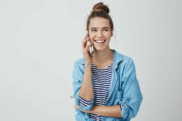 Hermosa mujer europea femenina riendo hablando por teléfono casualmente