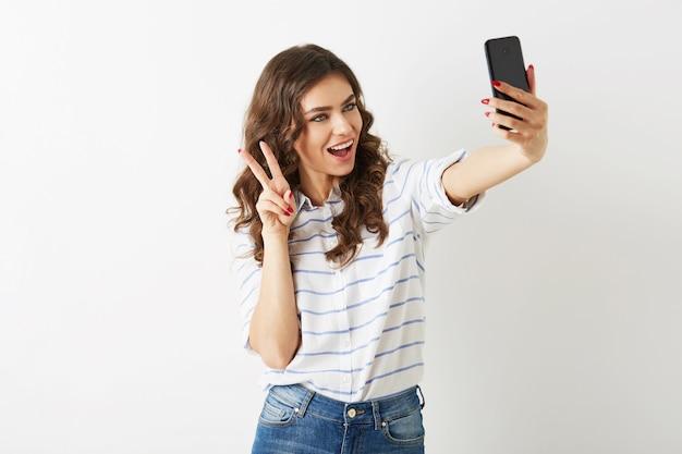 Hermosa mujer con expresión de la cara divertida haciendo foto selfie en teléfono móvil, sonriente, feliz, islolated, pelo rizado, estado de ánimo positivo, estilo hipster estudiante