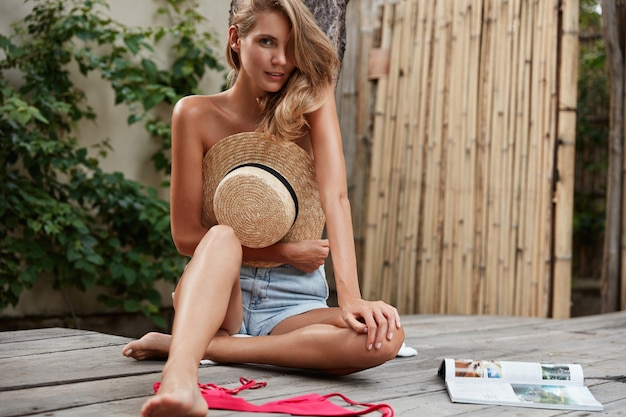 Hermosa mujer con expresión misteriosa, usa pantalones cortos de mezclilla, se quita el bikini, esconde el cuerpo desnudo con un sombrero de paja, se sienta en un piso de madera, lee una revista, disfruta del tiempo de recreación. ocio y estilo de vida