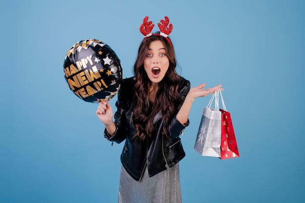 Hermosa mujer con feliz año nuevo globo y regalos en coloridos bolsos de compras aislados sobre azul