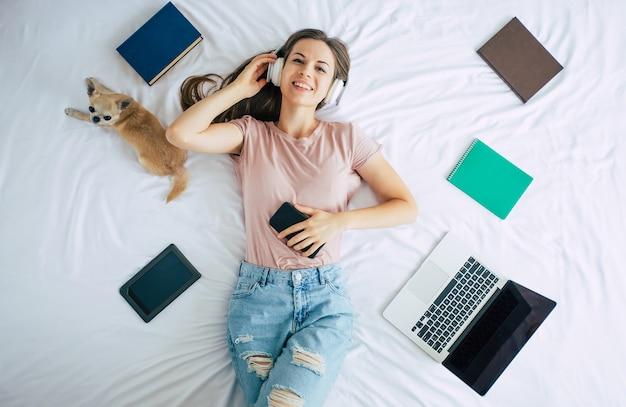 Hermosa mujer feliz en auriculares está acostada en la cama con su lindo perrito y escuchando música