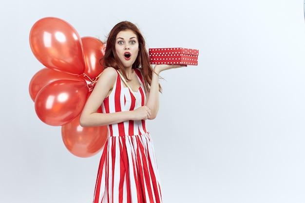Hermosa mujer feliz con bolas de aire rojo y un regalo