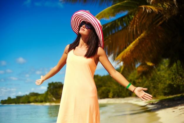 Hermosa mujer feliz en coloridos sombrero para el sol y vestido caminando cerca de la playa del océano en un caluroso día de verano cerca de la palma