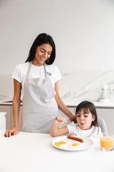 Hermosa mujer feliz en delantal de pie en kichen y haciendo el desayuno para su pequeña hija en la mañana