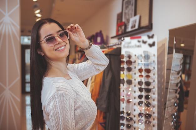 Hermosa mujer feliz disfrutando de las compras en la tienda de ropa