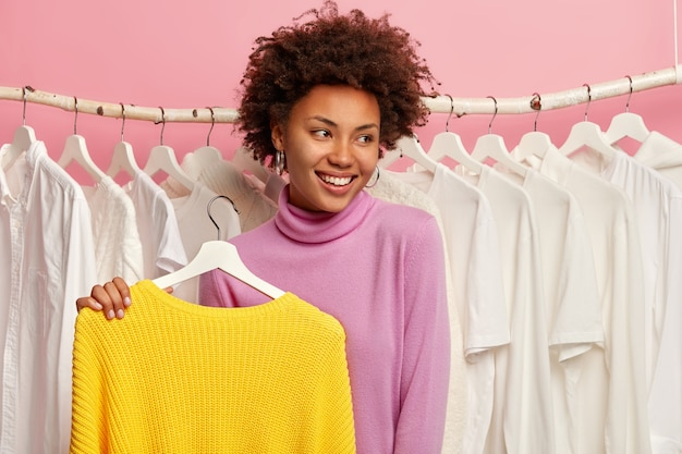 Hermosa mujer feliz elige ropa en la tienda, mira con alegría a un lado, sostiene suéter amarillo en perchas