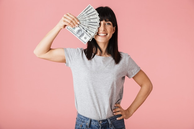 Una hermosa mujer feliz emocionada increíble posando aislada sobre la pared de la pared de color rosa claro con dinero.