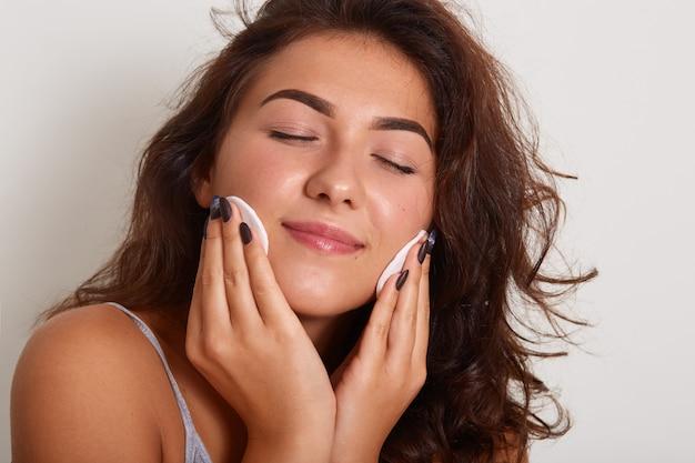 Hermosa mujer feliz con una piel sana perfecta limpiando su rostro con almohadillas de algodón, mantiene los ojos cerrados
