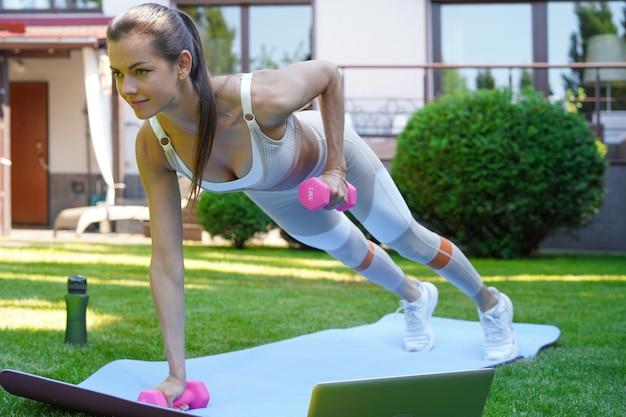 Hermosa mujer fitness haciendo un ejercicio de tabla viendo tutoriales en línea en la computadora portátil, entrenando al aire libre. estilo de vida saludable. chica practica deportes en el jardín.