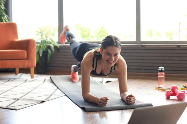 Hermosa mujer fitness haciendo un ejercicio de tabla viendo tutoriales en línea en la computadora portátil, entrenando en la sala de estar. estilo de vida saludable. chica practica deportes en casa.