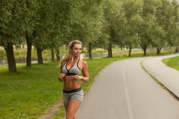 Hermosa mujer fitness saludable rubia en ropa deportiva de moda correr y practicar yoga en el parque al atardecer