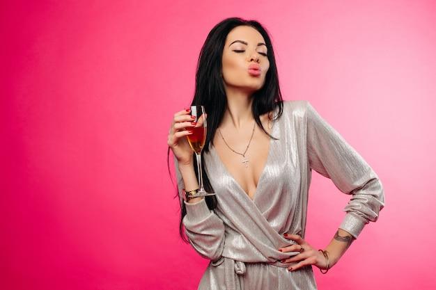 Hermosa mujer con flauta de champagne haciendo beso de aire con los ojos cerrados.
