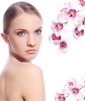 Hermosa mujer y flores de orquídeas