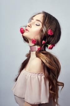 Hermosa mujer con flores rosas en su largo cabello