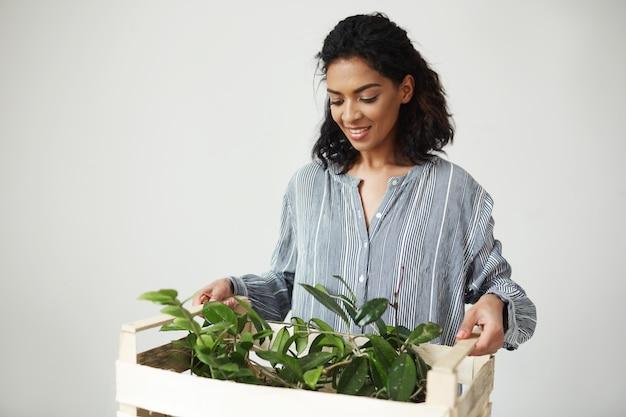 Hermosa mujer florista con caja de madera con plantas sobre pared blanca