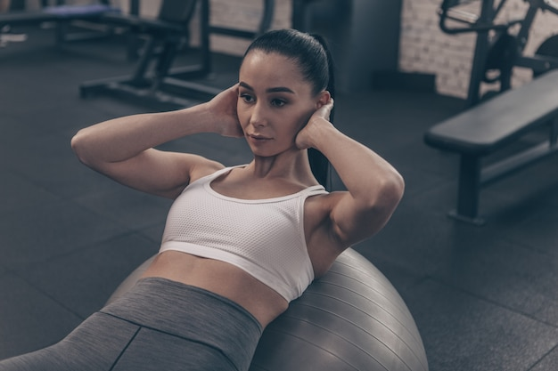 Hermosa mujer en forma haciendo abdominales en bola de fitness, ejercitándose en el gimnasio
