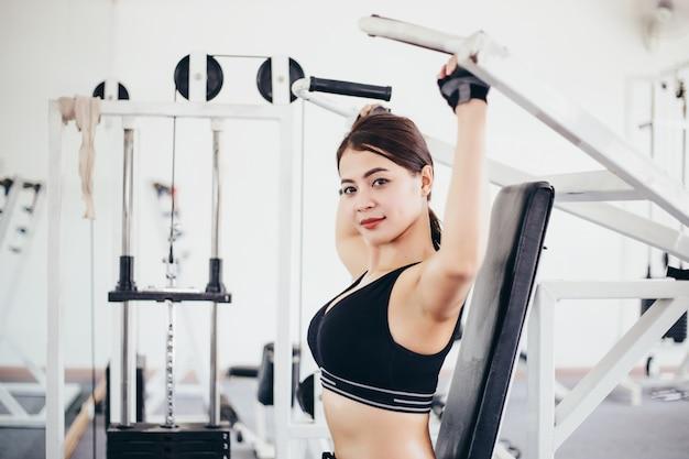 Hermosa mujer en forma muscular que ejercita la construcción de los músculos y la mujer haciendo ejercicios
