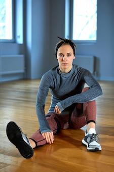 Hermosa mujer en forma en ropa deportiva posando mientras está sentado en el piso frente a la ventana en el gimnasio