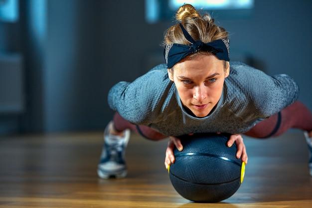 Hermosa mujer en forma en ropa deportiva posando mientras está sentado en el suelo con baloncesto frente a la ventana en el gimnasio estilo de vida y concepto de deporte saludable para niñas