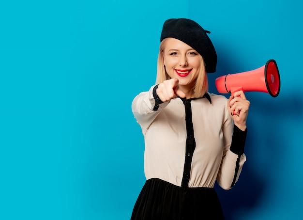 Hermosa mujer francesa en boina tiene ruidoso hailer en la pared azul
