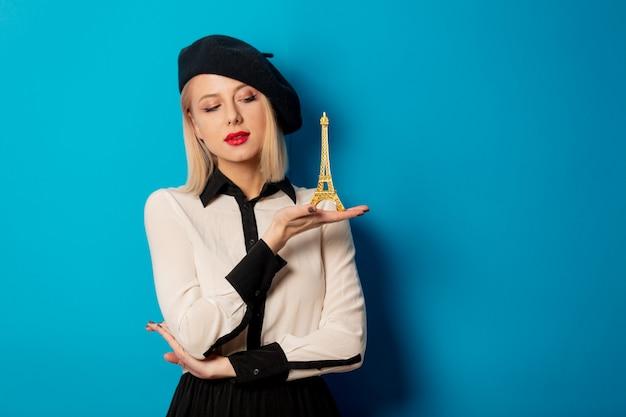 Hermosa mujer francesa en boina tiene torre eiffel en miniatura