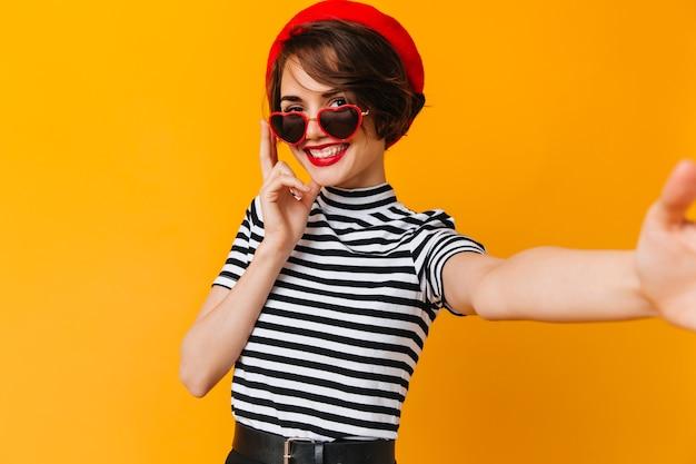 Hermosa mujer francesa con pelo corto tomando selfie