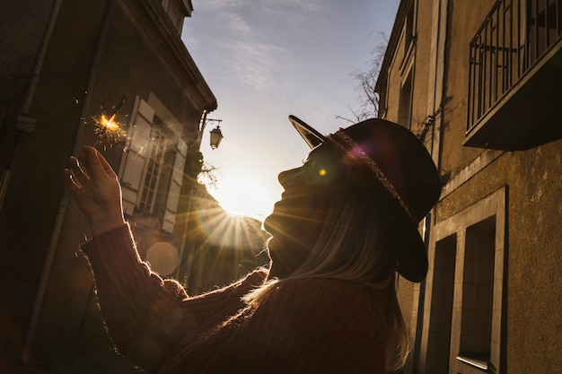 Hermosa mujer francesa sosteniendo un palo de chispa siendo iluminado con un encendedor